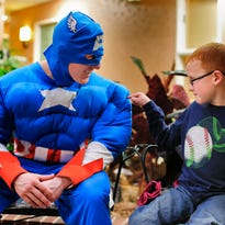 """Six-year-old Jaricho Jay touches the """"muscles"""" of Captain America, Nathaniel Morris, during a Super Hero Event at the Rainbow Senior Living on Saturday."""