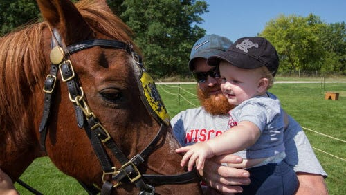 "Ben Brovold of Waukesha and his ten-month-old son Jack make friends with Caesar, the trusty steed ridden by Carlo D. Tuzzio of ""A Knight To Remember"", during his presentation on medieval knights, armor and weaponry at the Wisconsin Highland Games in Waukesha on Saturday, Sept. 5, 2015."