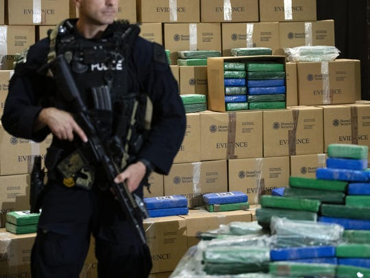 FILE - In this June 21, 2019 file photo, an officer stands guard over a fraction of the cocaine seized from a ship at a Philadelphia port that was displayed at a news conference at the U.S. Custom House in Philadelphia. Federal law enforcement officials raided a container ship at Philadelphia's port and discovered more than $1 billion worth of cocaine, one of the largest caches ever intercepted on U.S. shores. (AP Photo/Matt Rourke, File)