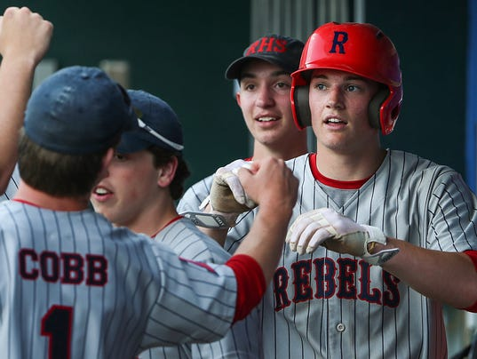 Roncalli Rebel Nick Schnell (7) is congratulated by teammates during Marion County tournament baseball final at Victory Field