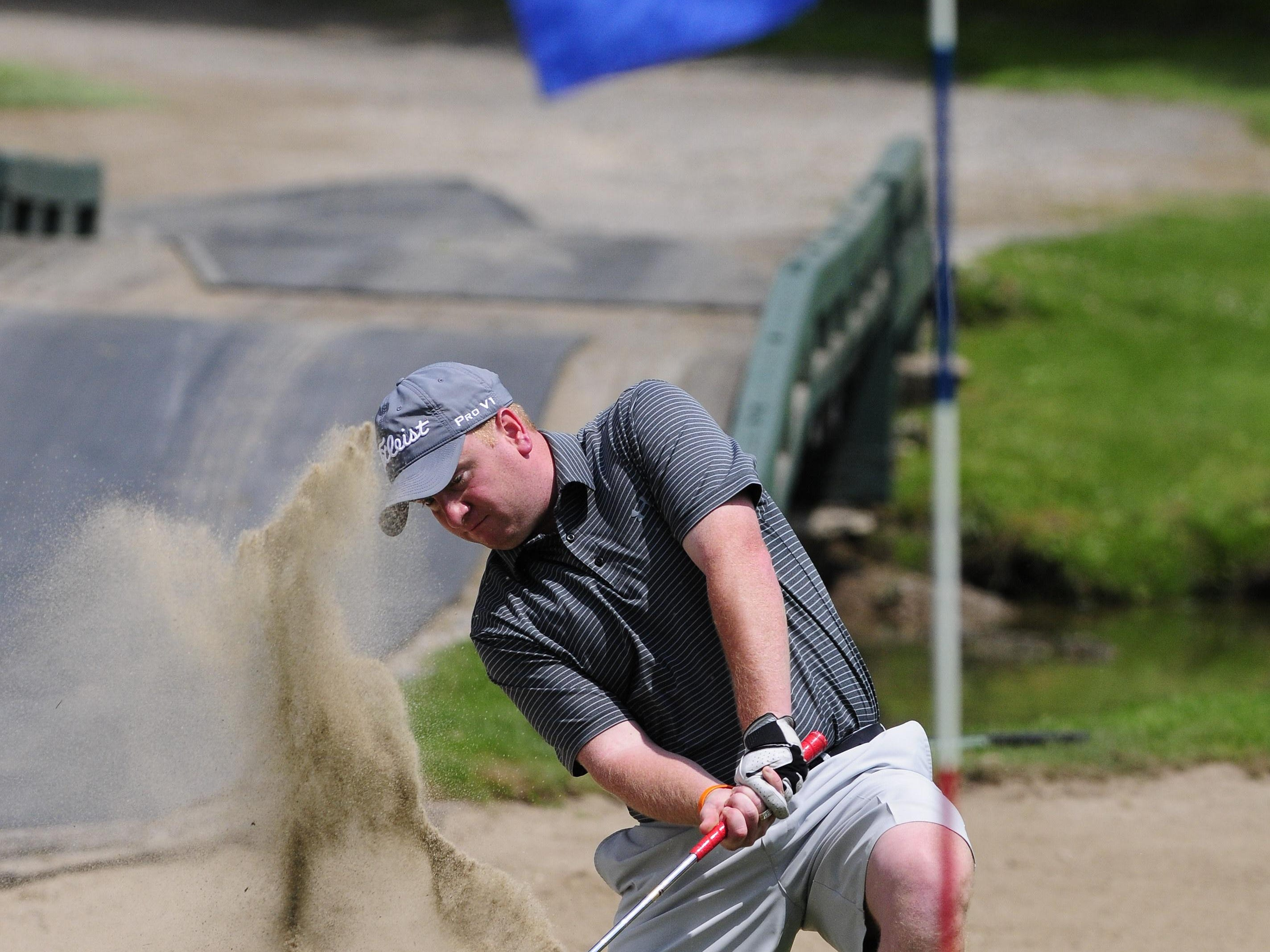 Mike Bush knocks his ball out of the sand bunker near the 18th green during the Port Huron Elks 2015 Men's Invitational in Port Huron Township.