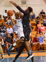 Rockledge's Saxon Williams (0) passes around the block of Melbourne's Rakeem Gillson (32) during Thursday's finals of the Rockledge Kiwanis Holiday Classic.