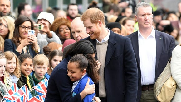 Prince Harry smiles as Meghan Markle hugs a young member