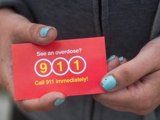 A woman standing outside Camden's City Hall in Roosevelt Park holds a card explaining the state's Good Samaritan law, which allows users to call 911 if they witness an overdose without fear of arrest or prosecution for drug possession or use.
