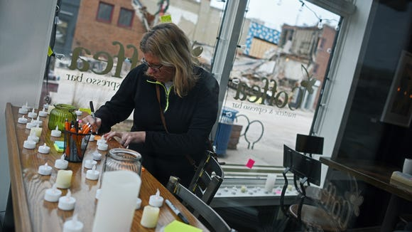 Amy Butler, of Sioux Falls, leaves a note at a memorial