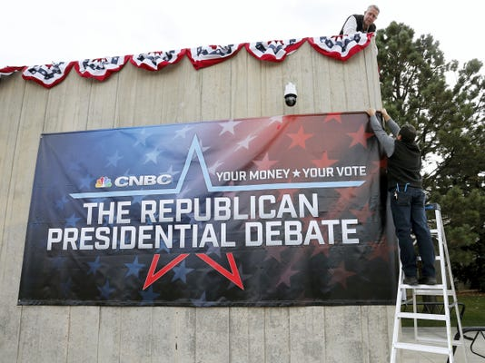 University of Colorado facilities management employees Robert Schumaker, right, and Jon Klarich put up a banner outside the Coors Events Center, the venue for the Oct. 28 Republican presidential debate, at CU Boulder, Colo., Monday Oct. 26, 2015. Republican presidential candidates taking the debate stage Wednesday in Colorado are hoping to carry momentum from a 2014 U.S. Senate victory in this toss-up state where independent voters outnumber the electorate from both major parties. (AP Photo/Brennan Linsley)