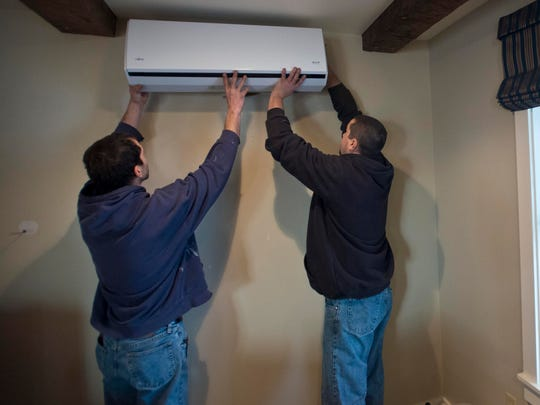 Joe Cobb and Nick Ramos of Energy Co-op of Vermont install a heat pump at the home of David Boucher in Essex, Nov. 21. .
