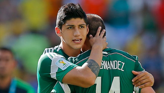 Mexico's Alan Pulido consoles teammate Javier Hernandez (14) after the Netherlands defeated Mexico 2-1 during the World Cup round of 16.