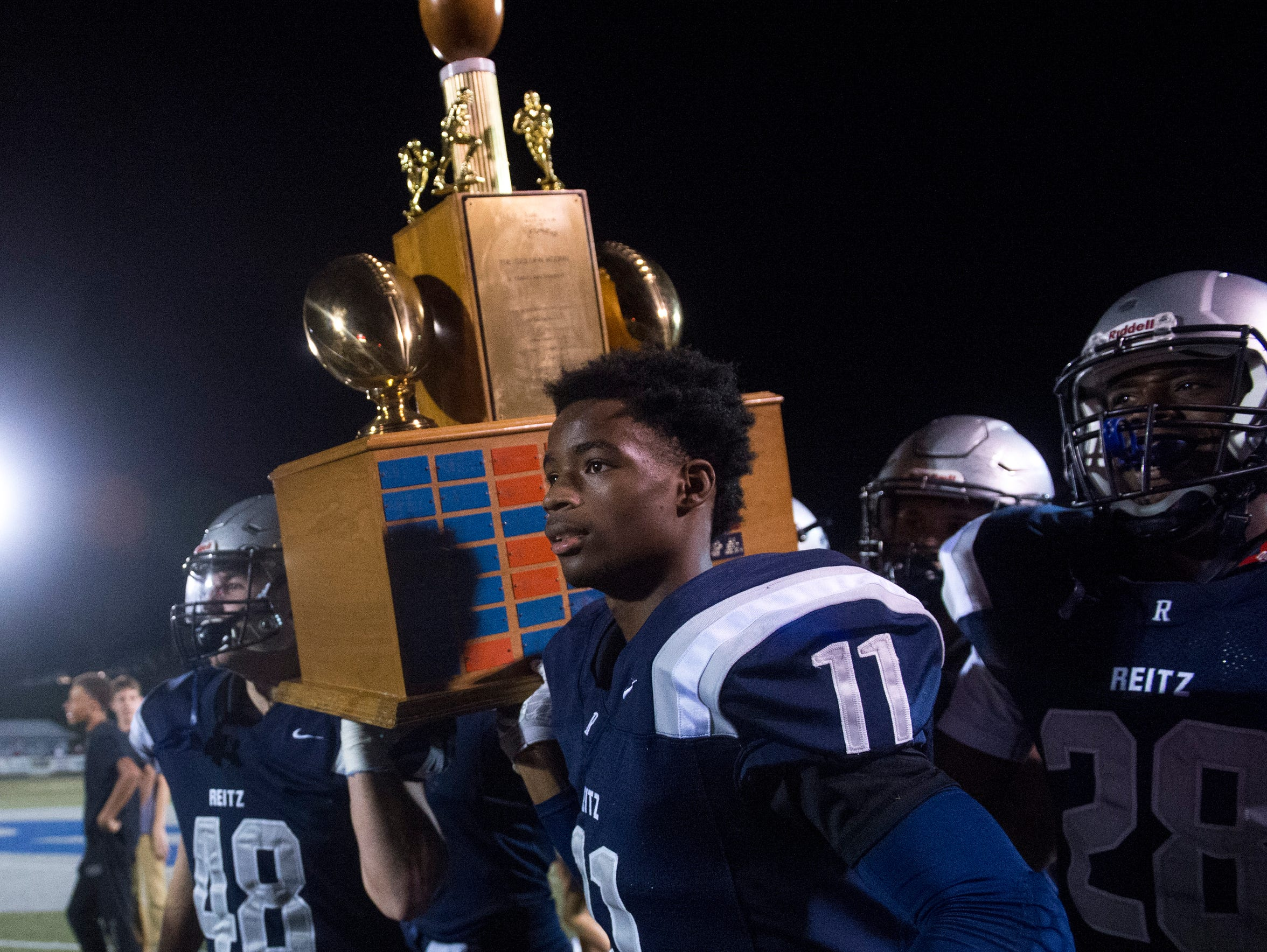 Reitz's Clayton Groves hoists the West Side Nut Club trophy after a wild 49-46 victory last year. The Panthers have won the last two matchups against rival Mater Dei.