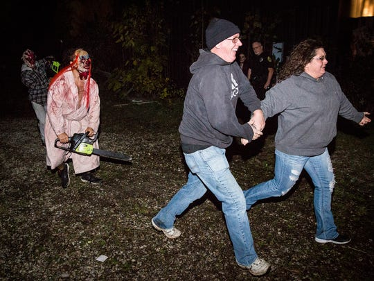 Visitors are chased out of the Scarevania haunted house by chainsaw wielding clowns in 2016.