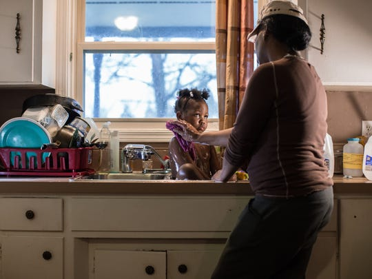 Ivory Gipson, 44, of Flint washes her daughter Marlana