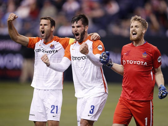 FC Cincinnati defender Dekel Keinan (21), Forrest Lasso (3) and goalkeeper Evan Newton (1) celebrate their win at the end  of their game at Lucas Oil Stadium on Saturday, March 31, 2018. FC Cincinnati defeated the Indy Eleven 1-0.