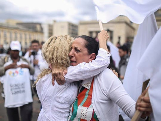 Women hug during a rally in support of the peace process with rebels of the Revolutionary Armed Forces of Colombia, FARC, a few blocks from the venue where Colombia's President Juan Manuel Santos and top FARC rebel leader Rodrigo Londono are signing a revised peace pact, at the main square in downtown Bogota, Colombia, Thursday, Nov. 24, 2016. An original accord ending the half century conflict was rejected by voters in a referendum last month.