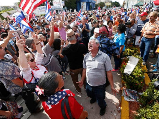 Members of the Cuban community react to the death of Fidel Castro, Saturday, Nov. 26, 2016, in the Little Havana area in Miami. Castro, who led a rebel army to improbable victory in Cuba, embraced Soviet-style communism and defied the power of 10 U.S. presidents during his half century rule, died at age 90.