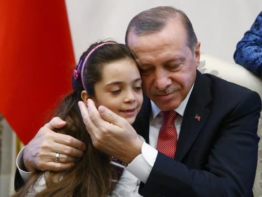 Turkey's President Recep Tayyip Erdogan, embraces Bana Al-Abed, 7, from Aleppo, Syria, at his Presidential Palace in Ankara, Turkey, Wednesday, Dec. 21, 2016. The Syrian child who became the civilian face of Aleppo – 7-year old Bana Al-Abed whose tweets of life under siege in Aleppo went viral and who was evacuated from Aleppo was greeted along with her family by Erdogan on Wednesday.