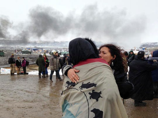 A couple embraces as opponents of the Dakota Access pipeline leave their main protest camp Wednesday, Feb. 22, 2017, near Cannon Ball, N.D., as authorities were preparing to shut down the camp in advance of spring flooding season. The Army Corps of Engineers ordered the camp closed at 2 p.m. Wednesday.