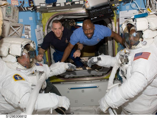 Former Detroit Lions wide receiver Leland Melvin, center, spent nearly 10 years training to be an astronaut and for his two missions to the International Space Station.
