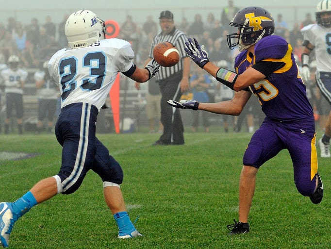 Two Rivers's Derek Schrimpf, right, and Roncalli's Cory Bahrs reach out for the pass intended for Schrimpf during their football opening game on Friday, Aug. 22, 2014 at Two Rivers High in Two Rivers. Matthew Apgar/HTR Media