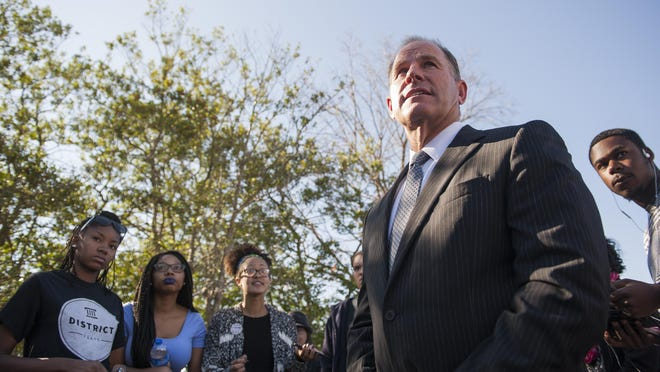 In a Tuesday, Nov. 3, 2015 photo, University of Missouri President Tim Wolfe speaks with members of Concerned Student 1950 senior Abigail Hollis, from left, senior DeShaunya Ware and junior Shelbey Parnell as they call for Wolfe's resignation outside University Hall on the University of Missouri campus, in Columbia, Mo. Long-simmering protests at the University of Missouri over matters of race and discrimination got a boost over the weekend when at least 30 black football players announced they will not participate in team activities until the university system's president is removed. (Daniel Brenner/Columbia Daily Tribune via AP)