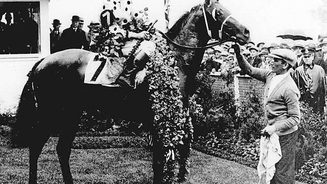 Earl Sande poses with Gallant Fox following his Triple Crown achievement in 1930.