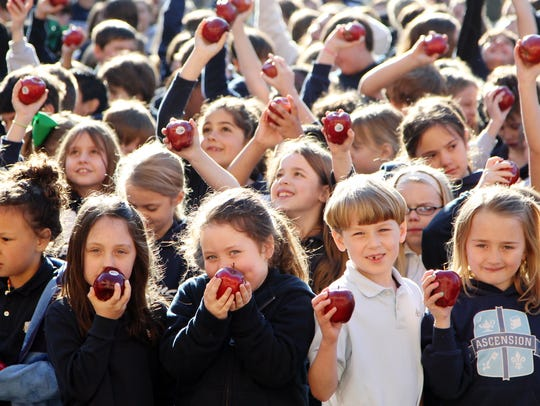 Ascension Episcopal School students hold up apples