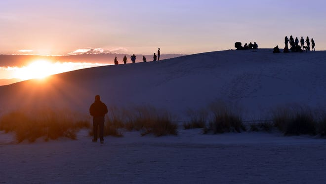 In this 2017 file photo, visitors watch the sunrise from atop the White Sands National Monument dunes.