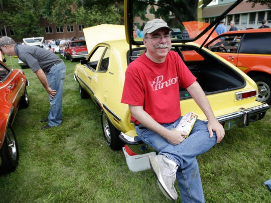 Chris Auger, 49, of Huntington Woods sits on the bumper of his 1976 Pinto as Ford Employees get a break to check out unique cars including Pintos at the Ford Product Development Center in Dearborn Friday, July 18, 2014. Pinto owners will participate in a trip to Hell, Michigan, on Saturday.