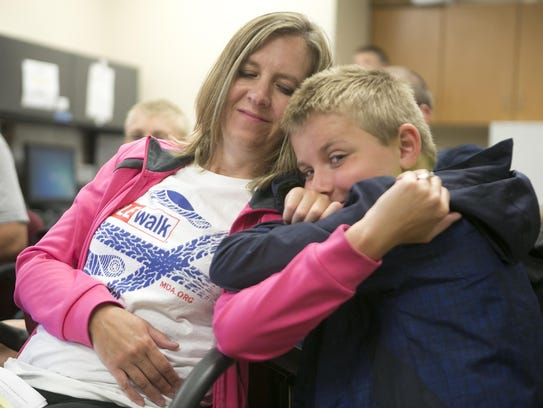 Jennie Kapral of Wild Rose, left, sits with her son