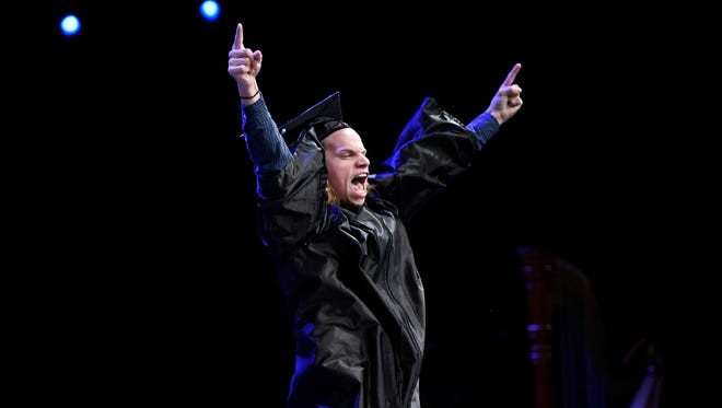 A graduate celebrates as he crosses the stage during the Nashville School of the Arts commencement at the Grand Ole Opry House Monday May 16, 2016, in Nashville, Tenn.