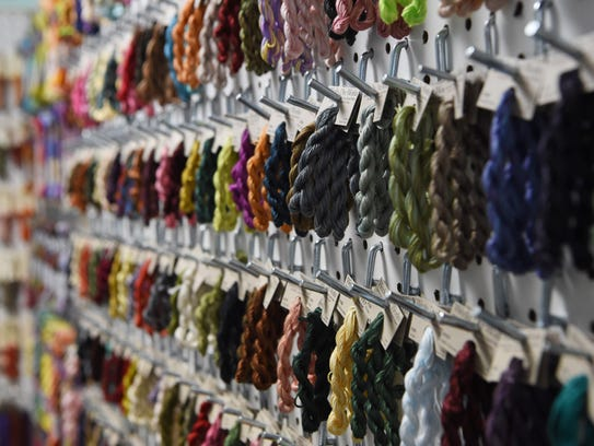 A variety of threads hang up in Deer Hill Farm Cross