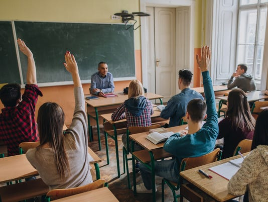 Group of teenage students with raised arms in the classroom.