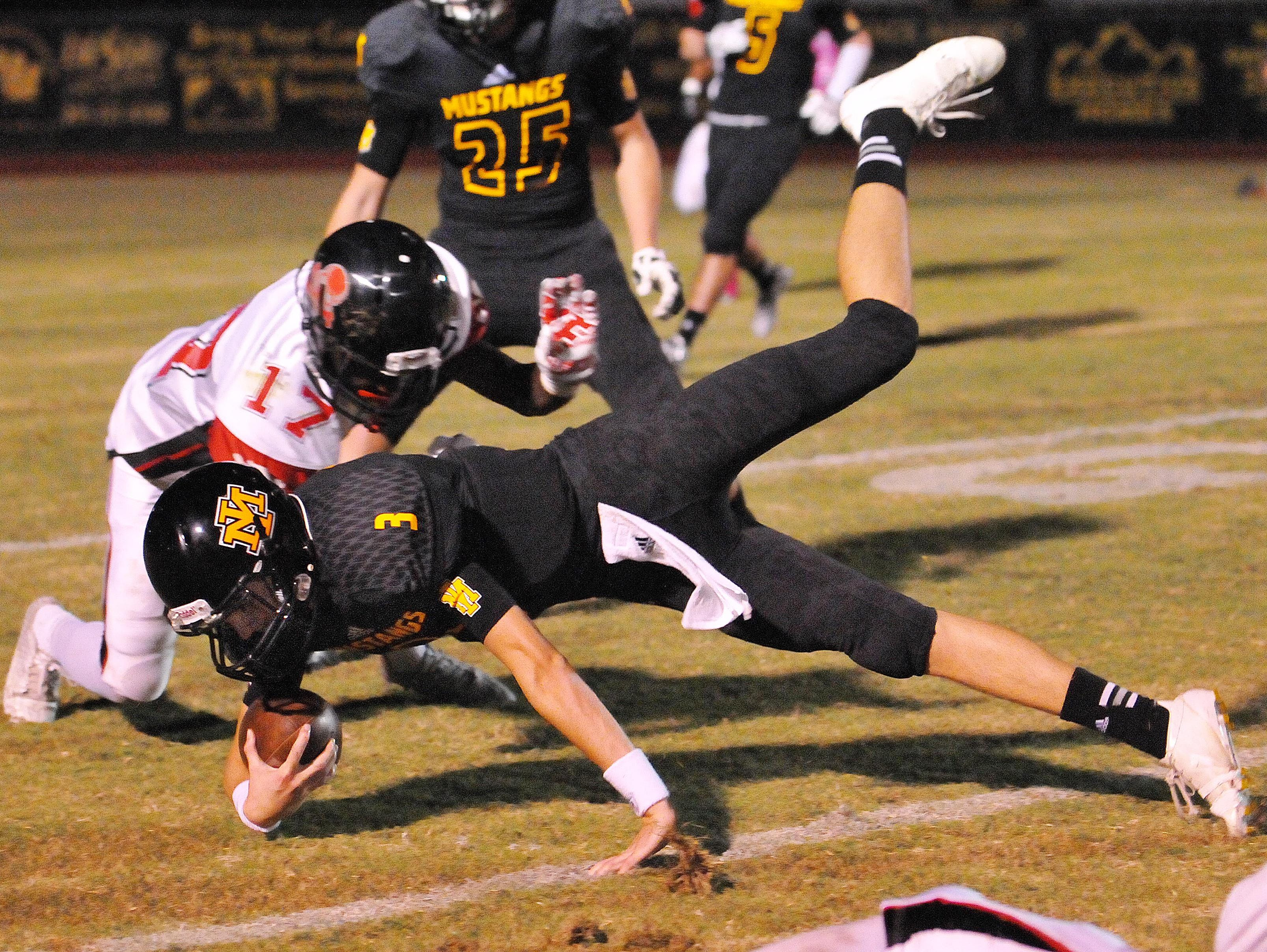 Merritt Island High QB Jimmy Batch is upended by Palm Bay High defenders during Friday night's game at Merritt Island High.