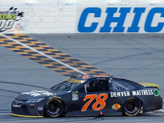 Martin Truex Jr. crosses the finish line as he wins a NASCAR Sprint Cup Series auto race at Chicagoland Speedway, Sunday, Sept. 18, 2016, in Joliet, Ill. (AP Photo/Nam Y. Huh)