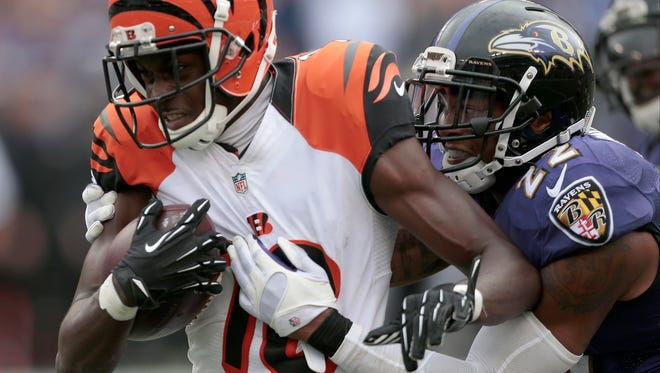 Cincinnati Bengals wide receiver A.J. Green (18) breaks a tackle as he runs for an 80-yard touchdown pass reception to regain the lead in the fourth quarter at Baltimore.
