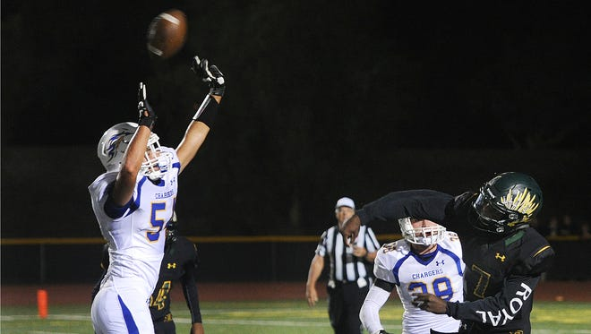 Agoura's Ben Tene, left, deflects a pass thrown by Royal quarterback Zeke Savage of during Friday night's game at Royal High. Agoura won 44-28.