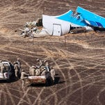 Egyptian military on cars approach a plane's tail at the wreckage of a passenger jet bound for St. Petersburg in Russia that crashed in Hassana.