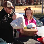 Joe Heflin, left, of Jefferson City, loads free groceries into his car last week with the help from a volunteer at a food pantry in Jefferson City, Mo. Heflin, 33, also gets food stamps, and he will lose that aid if he doesn't meet new work requirements or receive a disability exemption.