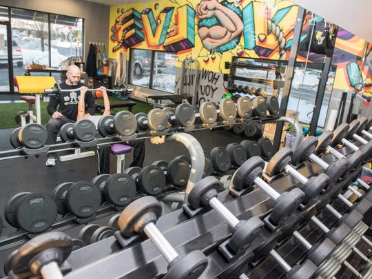 A rack of dumbbells are reflected in the mirror at Evolve Training in Tinton Falls, where co-owner Billy Dawson works with Jen Carducci, Holmdel, on a tricep exercise.