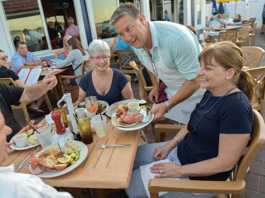 Doug Lentz, owner of Inlet Cafe in Highlands, serves dinner to Janice Conte of Long Branch (right). Seated to her left is Mary Wheeler of Long Branch.