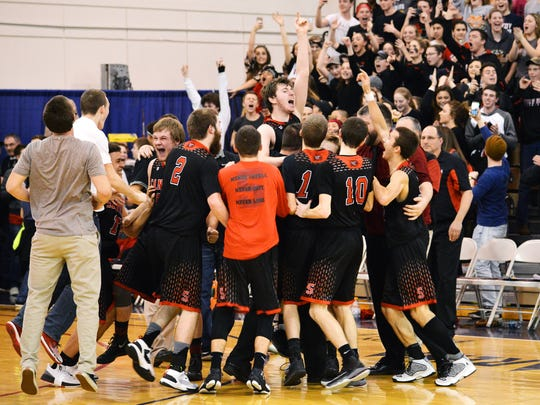 The Santiam boys basketball team celebrate after defeating Stanfield 57-54 in the state 2A basketball championship game on Saturday in Pendleton.
