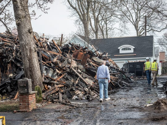 Officials investigate the aftermath of the fire. An