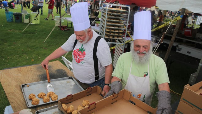 Beacon Sloop Club members Vince Farina (right) and Tom Schmeelk (left) move the biscuits off of the hot trays. Volunteers made strawberry shortcakes from around 1,500 pounds of strawberries.