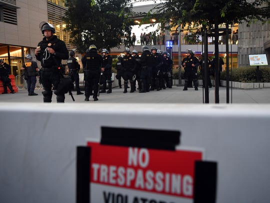 Police officers gather behind a barricade before a