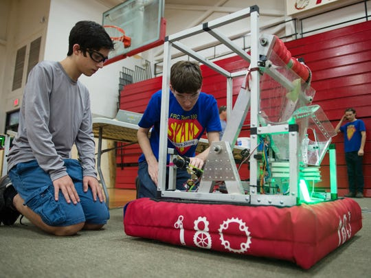 "SPAM members Lucas DeBonet, 15, left, part of the programming team, works with Tyler Woods, 18, the driver and SPAM team captain, as they test their robot, 'Buzz Lightgear,"" at South Fork High School."