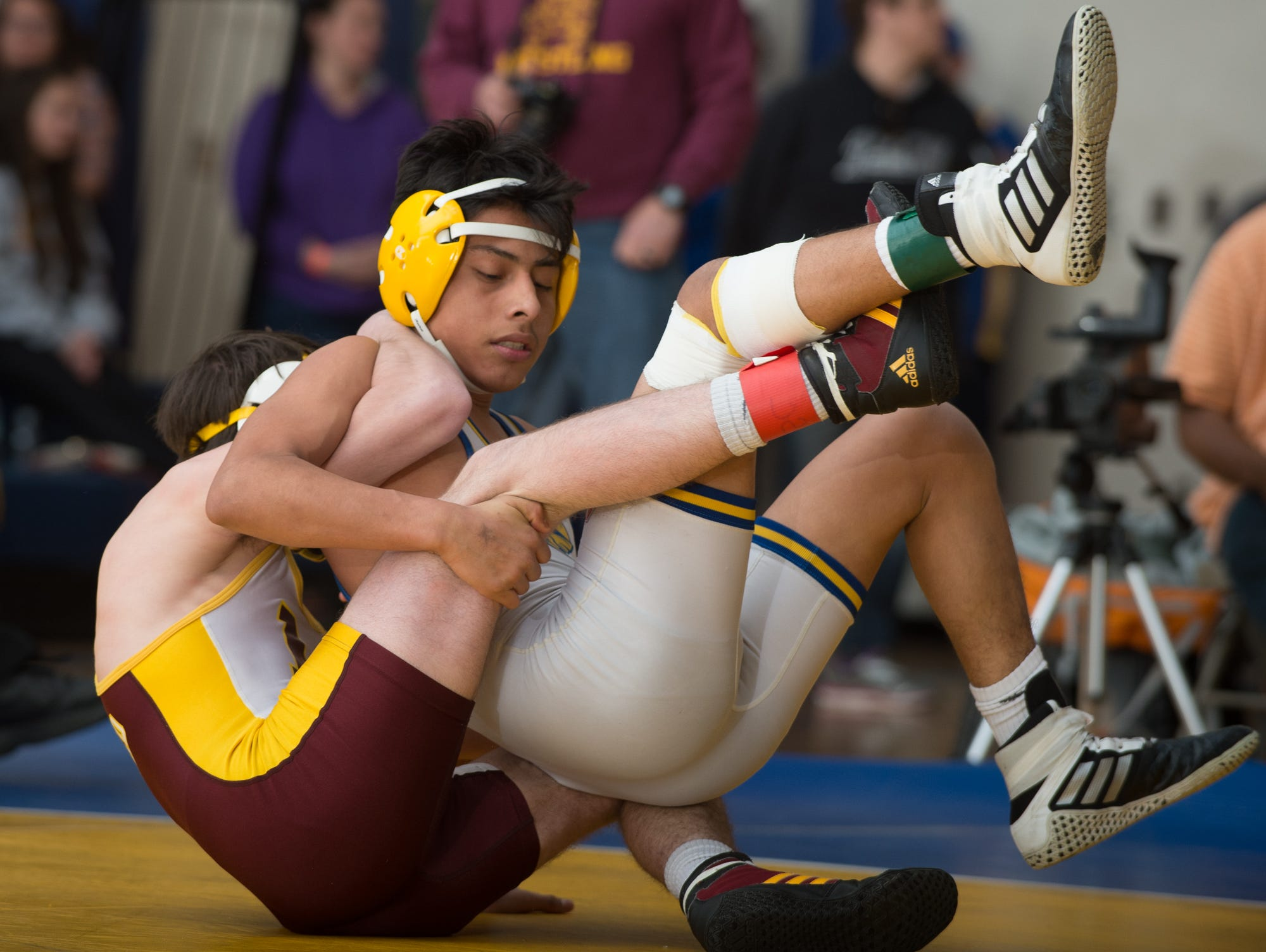 Milford's Robbie Rosser, left rolls over Sussex Central's Yony Morales in the 113 pound championship match at the Henlopen Conference wrestling tournament at Sussex Central High School.