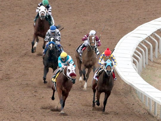 Blamed, left, with jockey Ken S. Tohill atop, rounds the last turn on its way to a first-place finish in the 18th running of the Sunland Oaks at Sunland Park Racetrack and Casino.