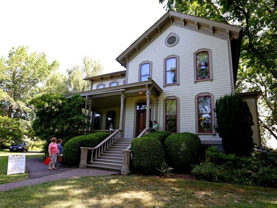 Visitors walk around the outside of Bush House Museum during the 66th annual Salem Art Fair & Festival at Bush's Pasture Park, on Friday, July 17, 2015, in Salem, Ore.