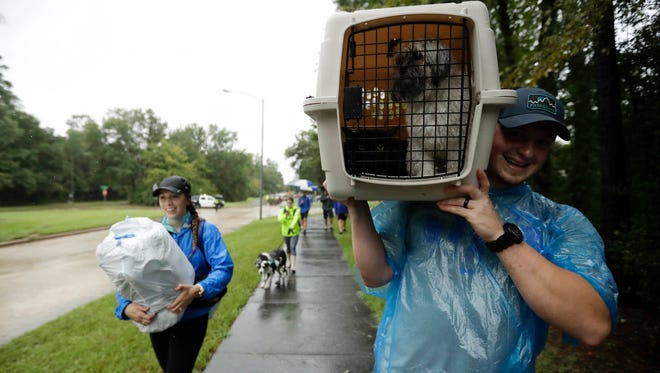 Jessie Rall carries his pets as he walks with his wife Montana Roll after being rescued by boat from their home among floodwaters from Tropical Storm Harvey Tuesday, Aug. 29, 2017, in Kingwood, Texas.