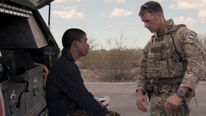 """A migrant, left, seeks help in Tucson's desert in a moment from """"Immigration Nation."""""""