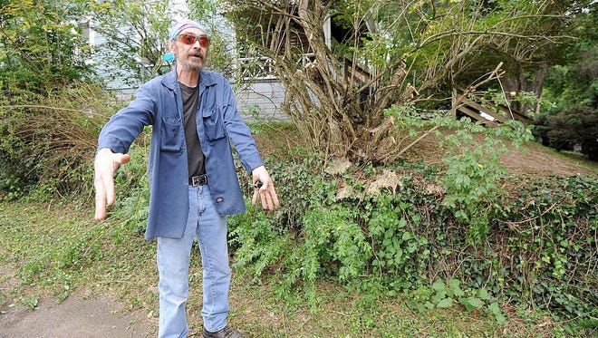Dave Holbrook of 230 Westbrook Avenue is upset about the damage done to his hedges when the city cut into them Wednesday evening.